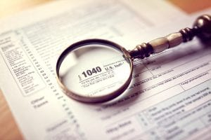 Income tax 1040 us individual tax return form and magnifying glass - Los Angeles bankruptcy attorney