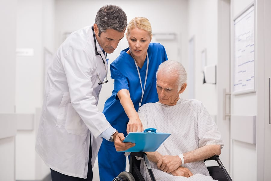 Los Angeles estate planning lawyer - Doctor and nurse with senior patient in wheelchair at hospital corridor talking. Mature doctor showing and discussing medical report with nurse and senior disabled at medical clinic.