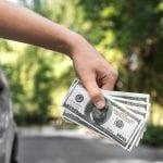 man-holding-money-in-car