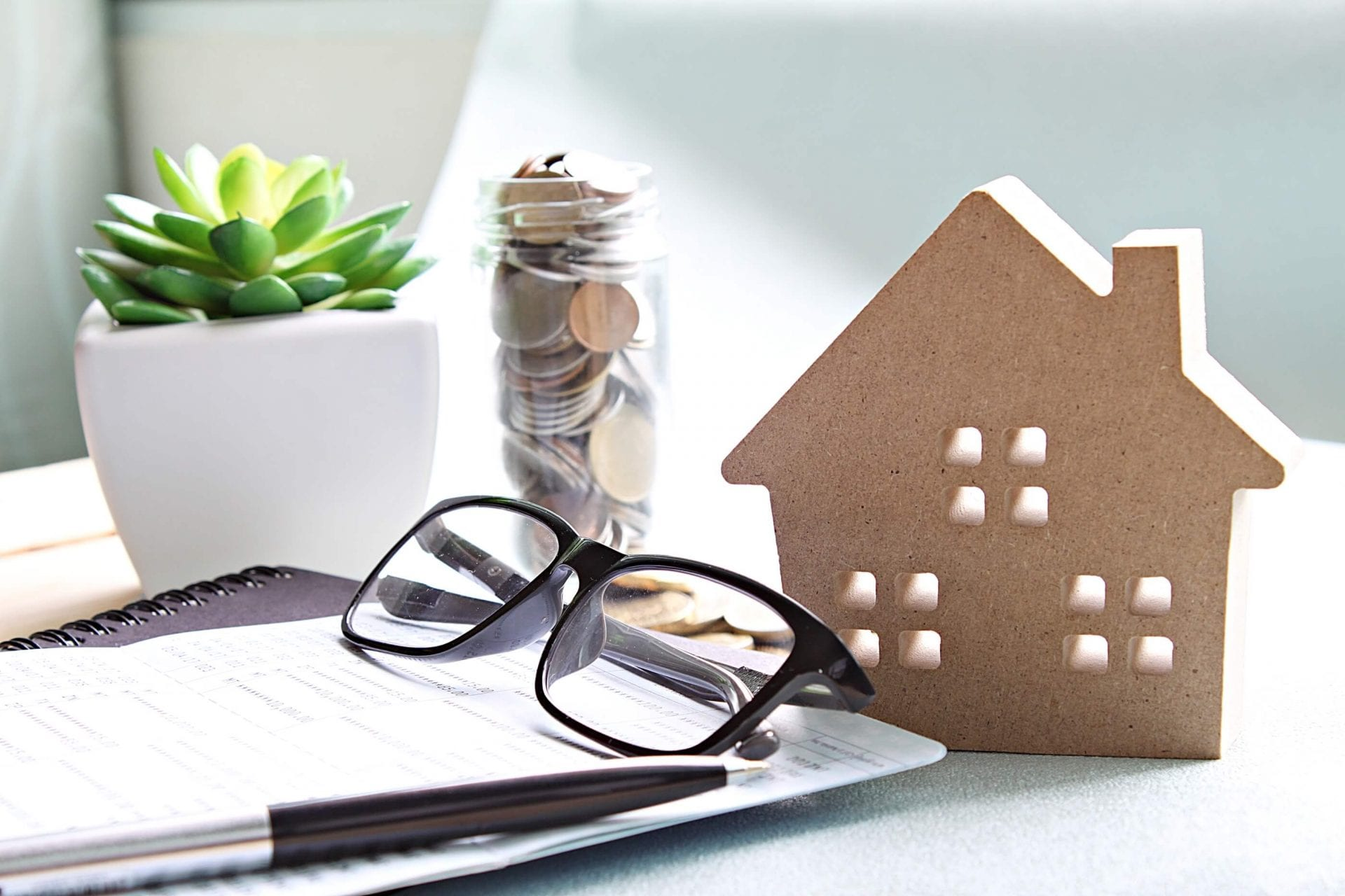 Pair of Black Glasses and Pen on Notebook on Desk with Potted Plant Jar of Coins and House Shaped Decoration