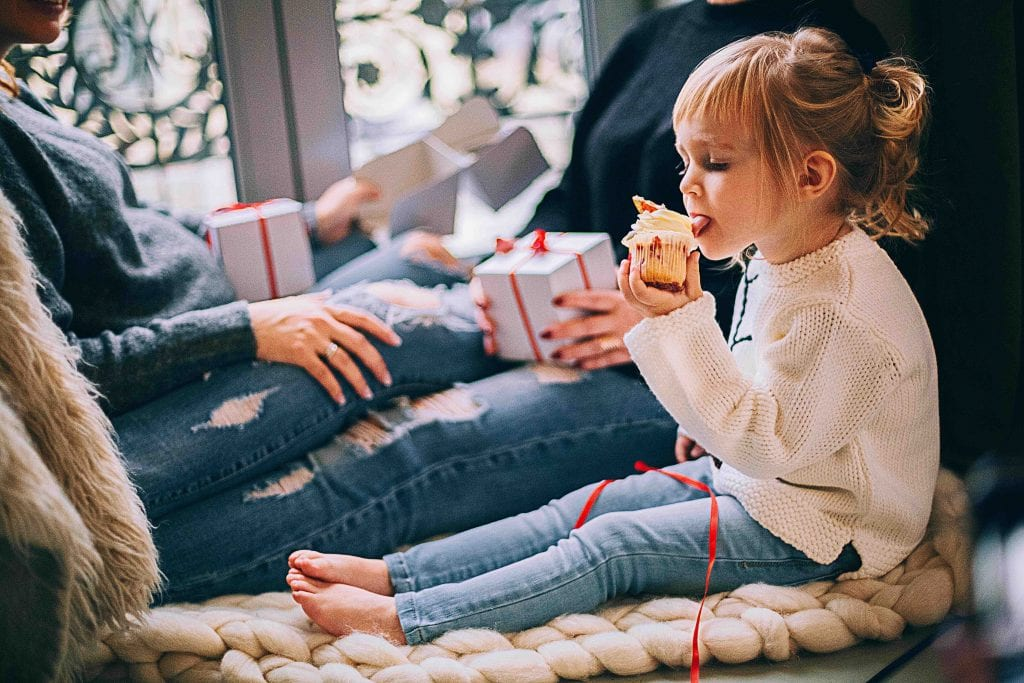 girl-eating-cupcake-while-sitting-beside-woman-in-blue-denim