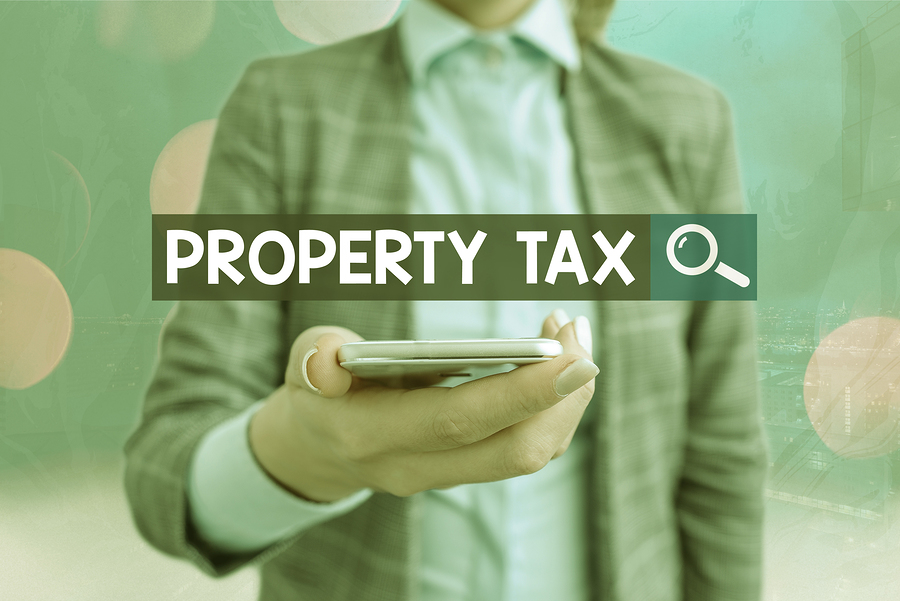 Property-Tax-green-background-man-holding-calculator