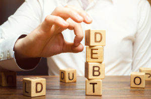 Businessman-Removes-Wooden-Blocks-with-the-Word-Debt