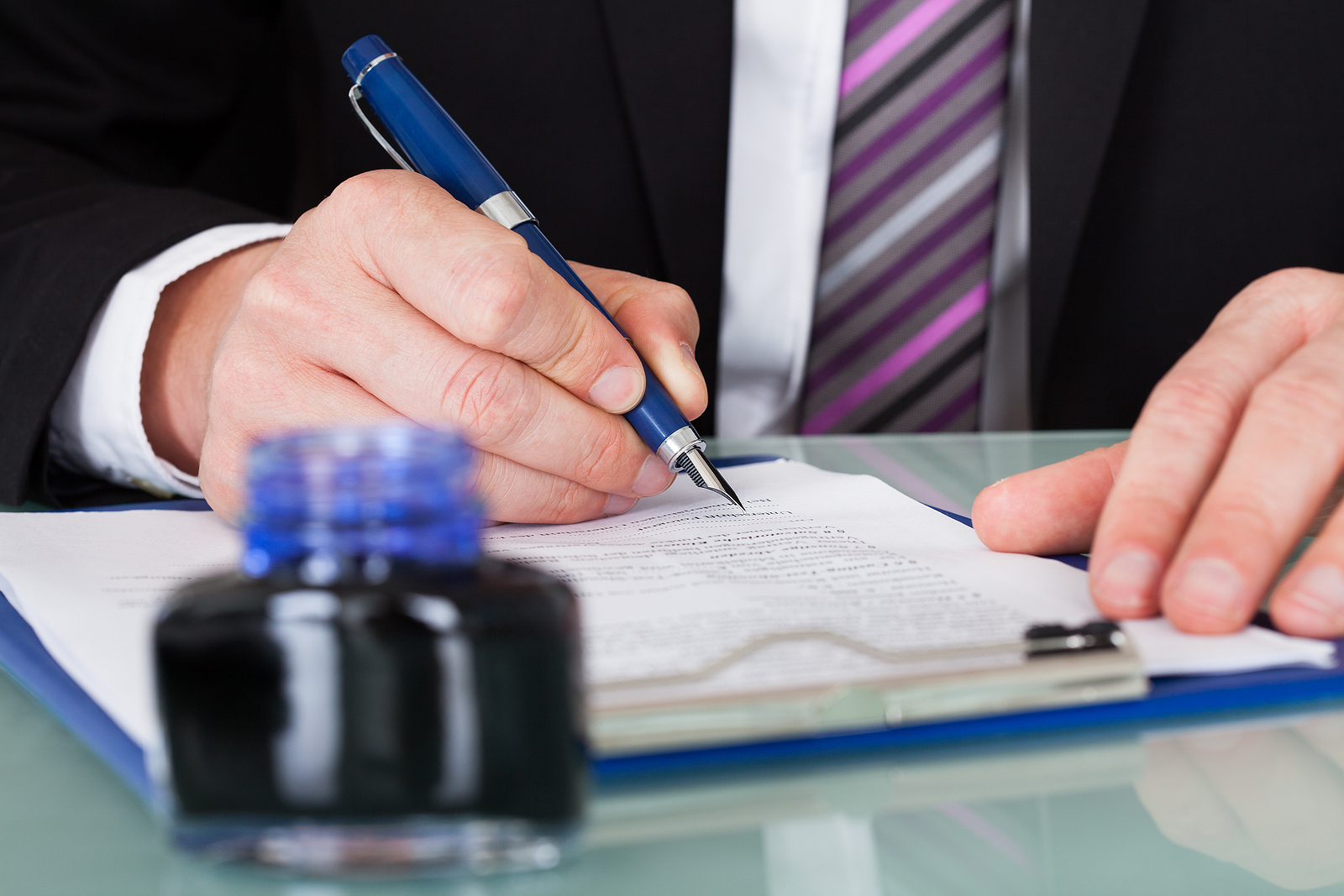 Close-up-of-Businessman-Writing-With-Ink-Pen-Over-Document
