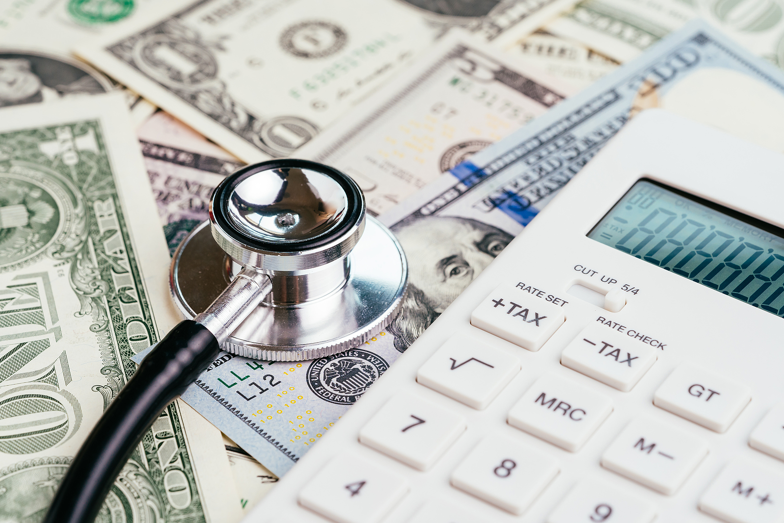 Doctor-Stethoscope-Placed-on-Pile-of-US-Dollar-Bills-Next-to-Calculator